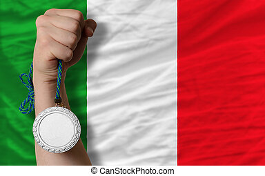 Silver medal for sport and national flag of italy - Holding...