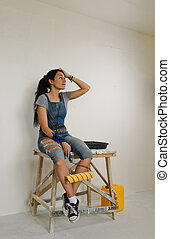 Woman taking a break from painting sitting on a wooden...
