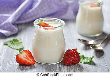yogurt with ripe fresh strawberry in jars on wooden...