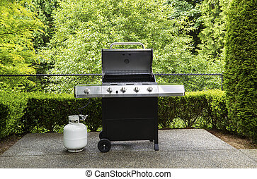 Outdoor cooker with lid in open position on home patio -...