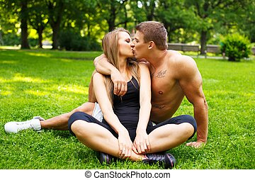 Young happy smiling sporty couple kissing on a meadow in a...