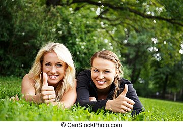 Two beautiful smiling girls lying on a grass in a park with...