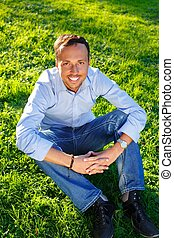 Happy handsome middle-aged man sitting on a grass outdoors