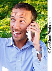 Happy handsome middle-aged man with mobile phone outdoors