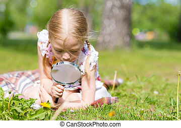 young scientist - girl in the park with a magnifying glass...