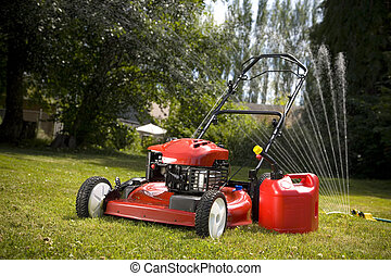 Red Lawn Mower - A red lawn mower and gas can in fresh cut...