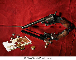 Protecting your savings concept - revolver and money on red...