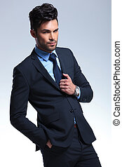 business man with hand on suit jacket - young business man...