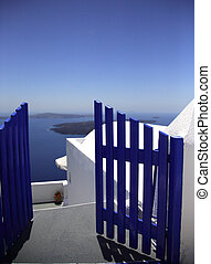 Blue gate leading you to the beautiful bay Santorini Greece