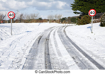 Snow tracks on a country road and 40 mph signs