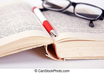 glasses and pen on the book