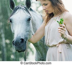 joven, mujer, acariciando, manchado, caballo