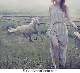 Delicate brunette posing with horse in the background -...