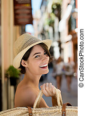 Laughing woman going shopping with a straw shopping back...