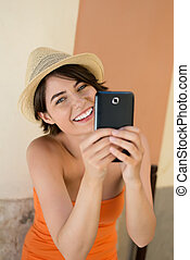Laughing young woman photographing herself - Laughing...