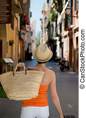Confident woman carrying a straw shopping bag walking away...