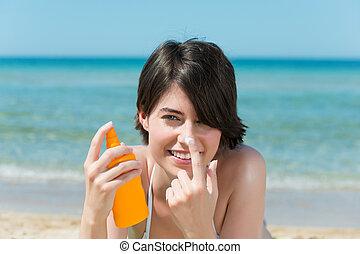 Beautiful woman applying sunscreen to her nose - Beautiful...