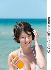 Woman with suntan lotion at the sea - Beautiful young woman...