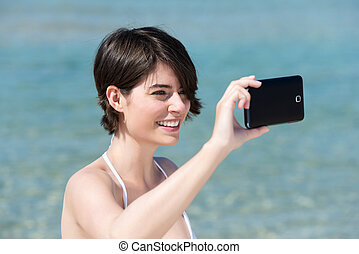 Woman photographing herself on her mobile - Attractive young...