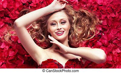 Smiling cutie among rose petals
