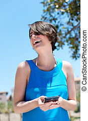 Woman laughing at the contents of an sms - Low angle view of...