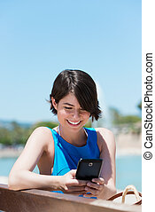 Woman reading an sms on her mobile - Pretty young woman with...