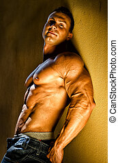 Handsome young bodybuilder against wall - Attractive and...