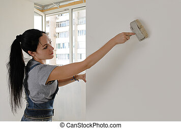 Attractive woman painting a house wall - Attractive young...
