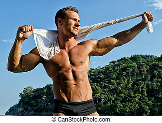 Handsome young bodybuilder with arms open in nature setting...