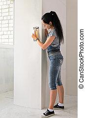 Woman resurfacing a wall - Capable young woman resurfacing a...