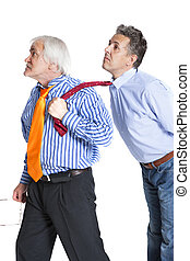 businessman pulling a tie to younger man - businessman...