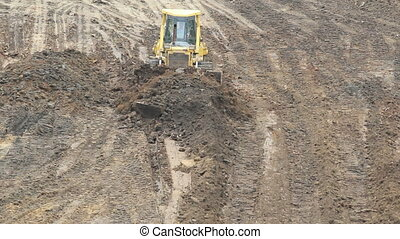 Yellow Bulldozer Raking Clay