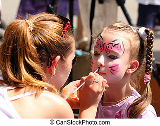 artist paints on face of little girl - artist paints...