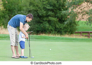 family of two at the golf course - young handsome father...