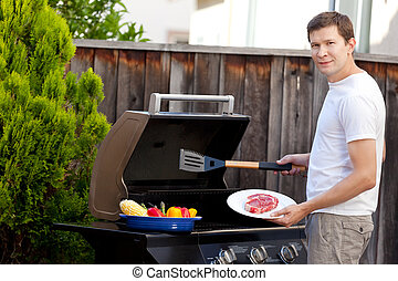 man grilling food - handsome young man ready for grilling...
