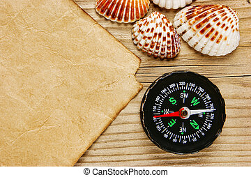 piece of paper and compass with sea shells on old wooden board