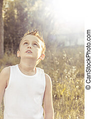 Child looks intrigued into the sky under the golden sun of...