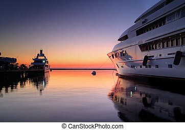 Superyacht at sunset - Extra Large Luxury yachts rest in the...