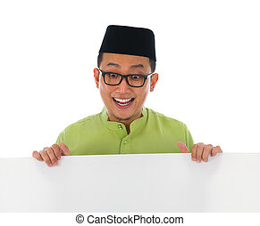 malay male with blank card during hari raya Eid al-Fitr...