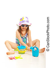Cheerful girl playing with beach toys