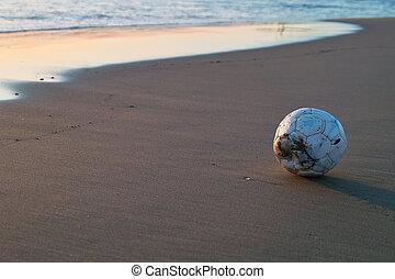 Soccer Ball near the sea at sunset