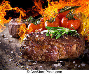 Delicious beef steak on wooden table with fire flames