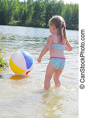 a little girl swims in the river.