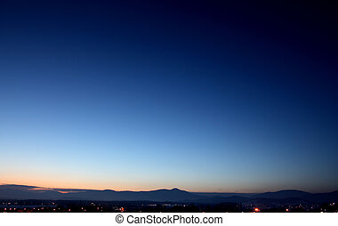 Sunrise behind the mountains - Very early sunrise view with...