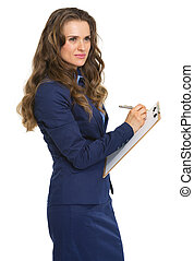 Thoughtful business woman writing in clipboard