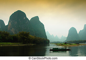 Fishing boat in calm waters amongst grotesque mountain...