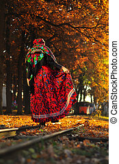 Romantic young gypsy woman walking on the railroad trying to...