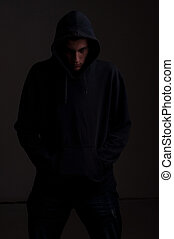 teenager with hoodie looking down against a dirty dark gray...