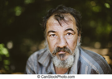 portrait of real hobo - real homeless man on the foliage...