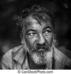 portrait of hobo - real homeless man on the dark background,...